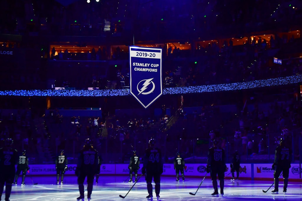 The Tampa Bay Lightning watch as the 2019-2020 Stanley Cup Championship banner is raised at Amalie Arena prior to a game against the Nashville Predators on March 13, 2021 in Tampa.
