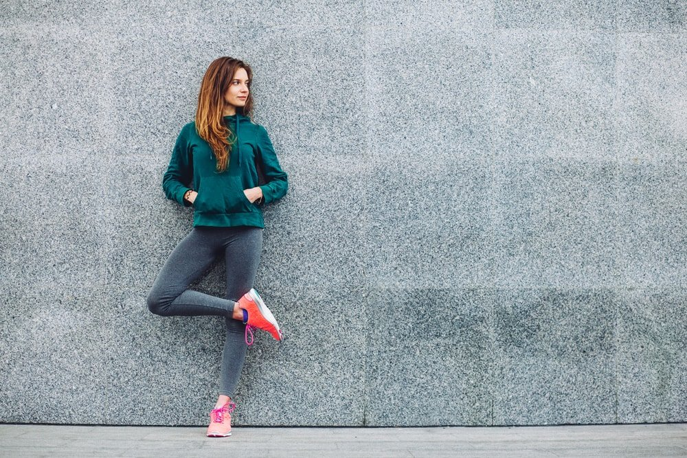 woman in activewear leaning against cement wall
